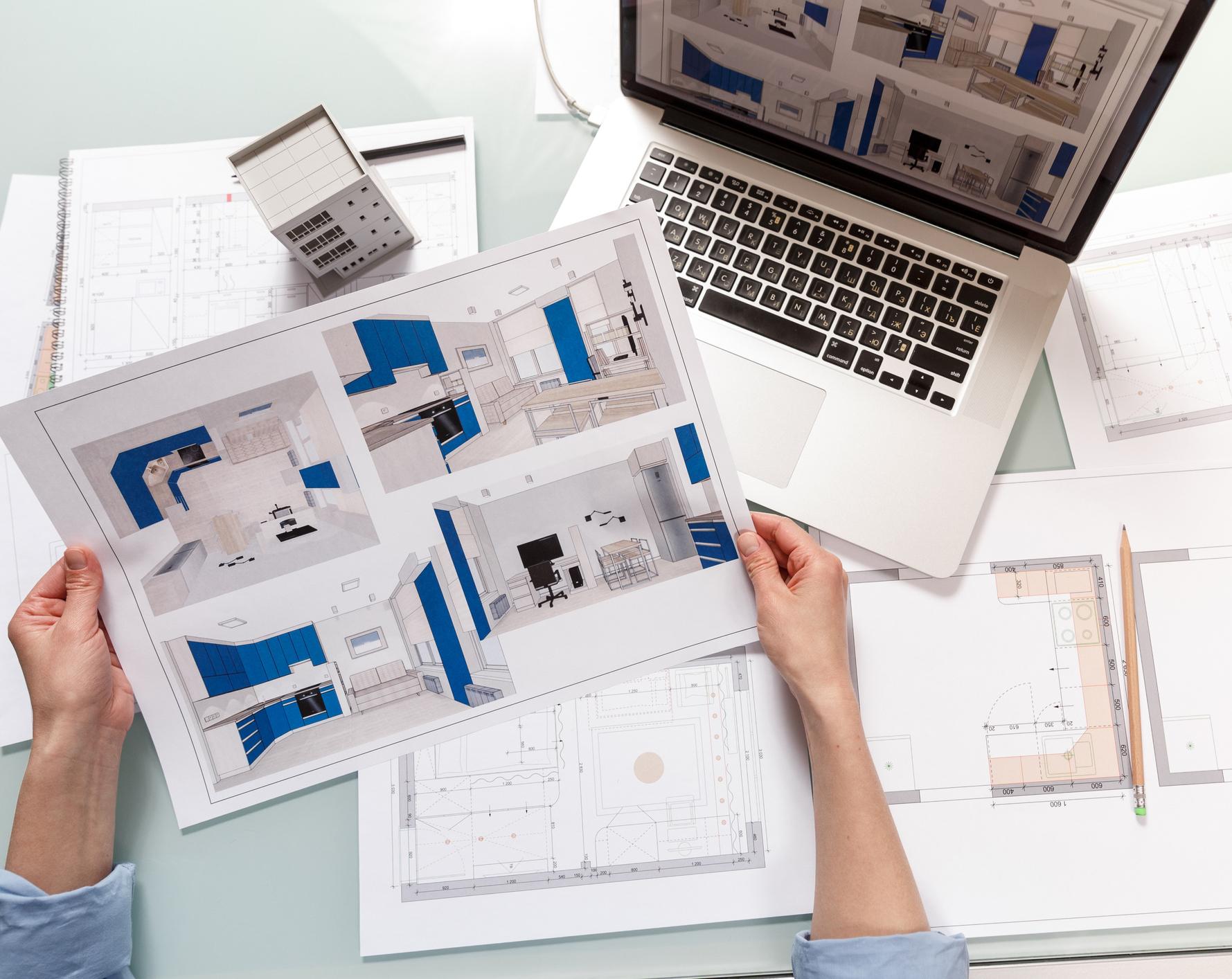 Interior designer working with a kitchen visual renderings in a design bureau.