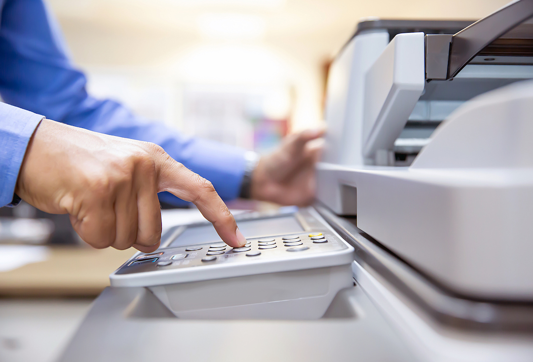 Businessmen press button on the panel of photocopier