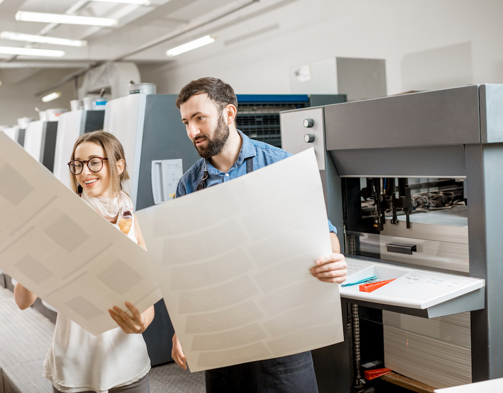 Woman with print operator at the printing manufacturing